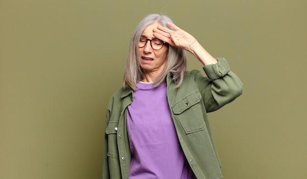 ストレス、疲れ、欲求不満を見て、額から汗を乾かし、絶望的で疲れ果てていると感じている年配の女性