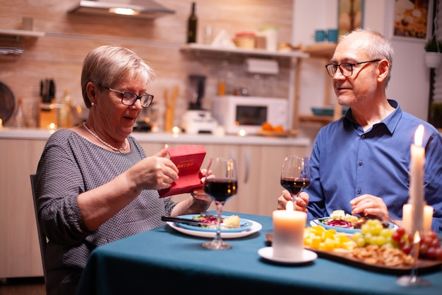 Senior woman looking surprised at gift box from husband during dinner in kitchen. happy cheerful elderly couple dining together at home, enjoying the meal, celebrating their marriage , surprise holida