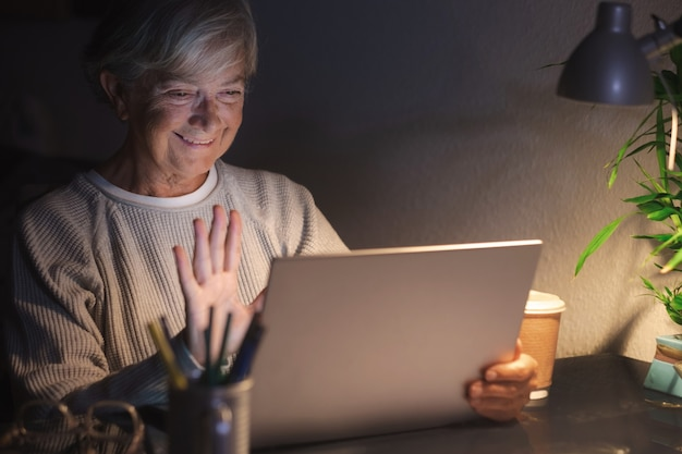 Senior woman looking and using laptop at home late night in videocall with family or friends