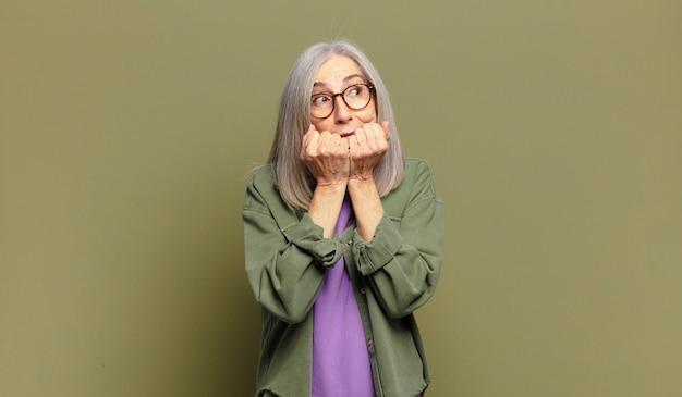 Пожилая женщина выглядит обеспокоенной, встревоженной, напряженной и испуганной, кусает ногти и смотрит в пространство для боковой копии