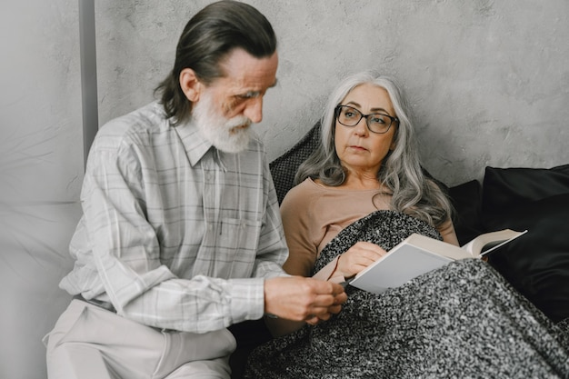 Senior donna sdraiata sul letto e prendendo pillole con marito premuroso. malattia, quarantena.