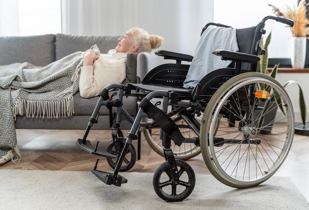 Старшая женщина, лежа в постели рядом с инвалидной коляской