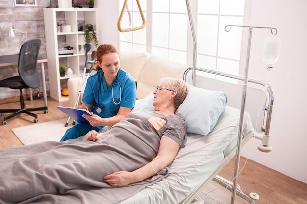 クリップボードにメモを取る女性医師と話しているナーシングホームのベッドに横たわっている年配の女性。