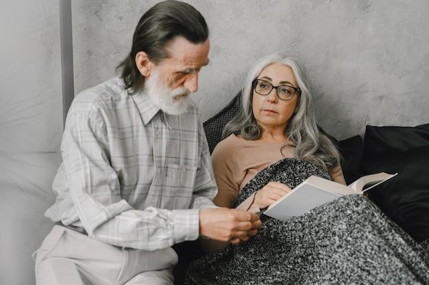 ベッドに横になって、思いやりのある夫と一緒に錠剤を服用している年配の女性。病気、検疫。