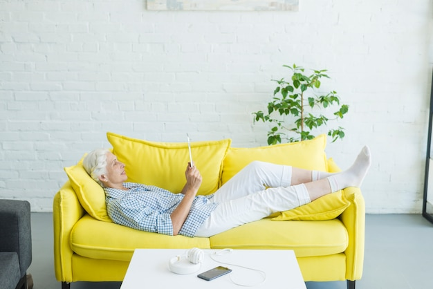 Senior woman lying on yellow sofa looking at digital tablet