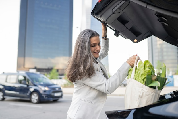 Senior woman makes the purchase and puts it in the trunk of the car