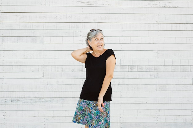 Senior woman making grimace over a white surface