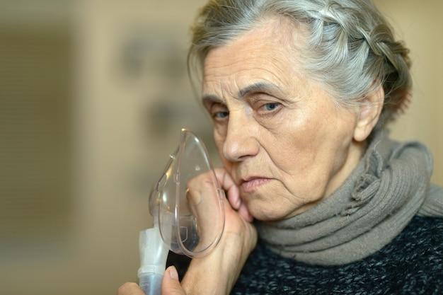 Senior woman making inhalation on dark background