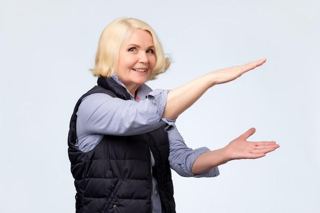 大きなサイズを示す年配の女性