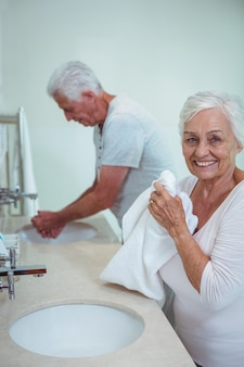 Senior woman and man cleaning hands in bathroom