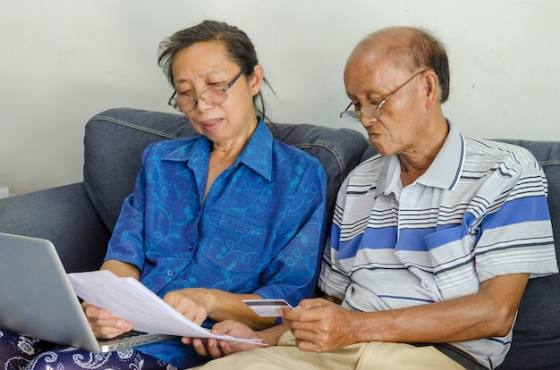 Senior woman and man looking business documents computer and credit card