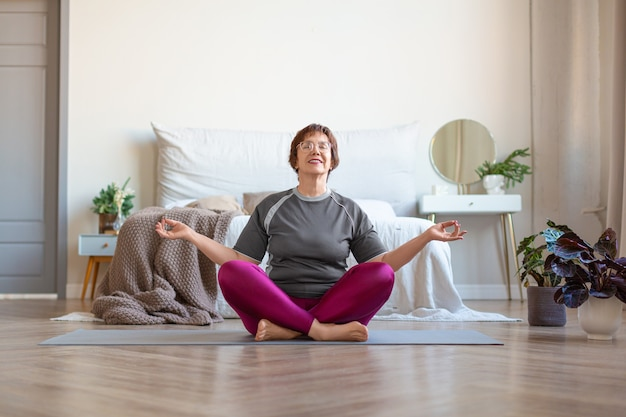 年配の女性は、自宅で蓮華座で瞑想します。若さを長引かせるためのヨガクラス。健康的なライフスタイルとアンチエイジングのコンセプト。