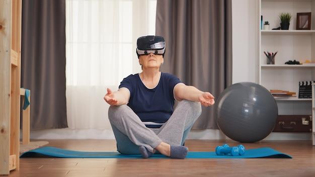 Старшая женщина медитирует на коврике для йоги, носить гарнитуру vr. активный здоровый образ жизни спортивный пожилой человек тренировки тренировки дома велнес и упражнения в помещении