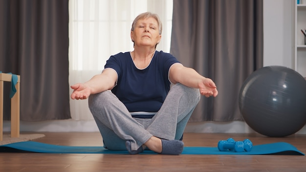 Старшая женщина медитирует, сидя на коврике для йоги в гостиной. активный здоровый образ жизни спортивный пожилой человек тренировки тренировки дома велнес и упражнения в помещении