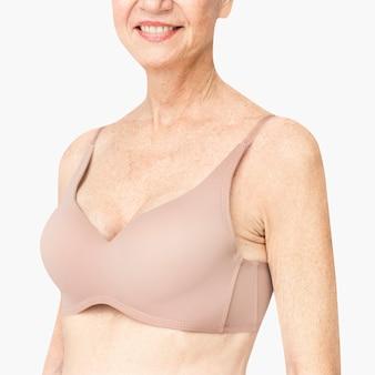 Donna anziana in reggiseno nudo con spazio di design