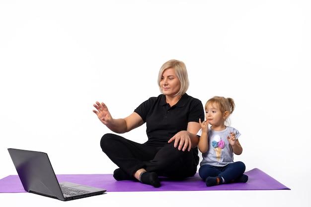 노트북 카메라 피트니스 온라인에서 손을 흔들며 그녀의 손녀와 함께 피트니스 매트에 수석 여자