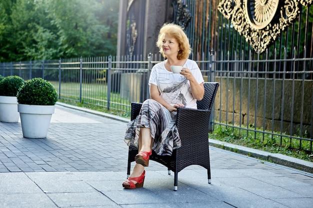ベンチで年配の女性が都市の庭でコーヒーを飲む