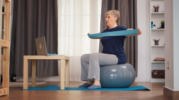 オンラインレッスンを見ているレジスタンスバンドでエクササイズしている安定ボールの年配の女性。オンライントレーニング学習技術老婆リフティングトレーニング健康的なライフスタイルスポーツフィットネストレーニング自宅でwi