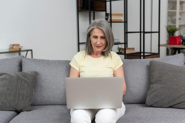 Старшая женщина на диване у себя дома с помощью ноутбука