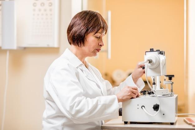 オフィスでビジョンハードウェアを扱う年配の女性眼科医