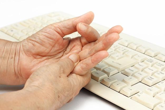 У пожилой женщины болит палец из-за длительного использования клавиатуры и мыши.