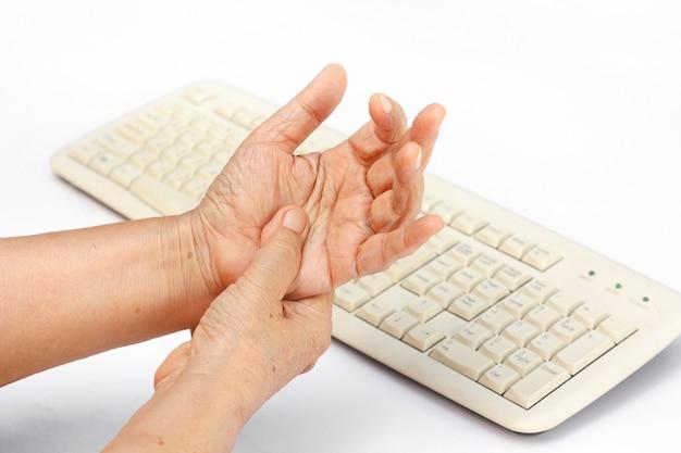 키보드와 마우스의 장기간 사용으로 인해 시니어 여성의 고통스러운 손가락.