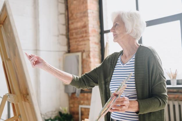 Senior woman painting in art studio