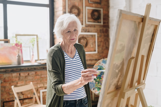 Senior woman painting pictures  in art studio