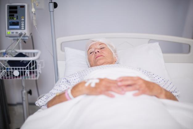 ベッドに横になっている酸素マスクを身に着けている年配の女性患者