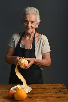 Senior woman peel orange