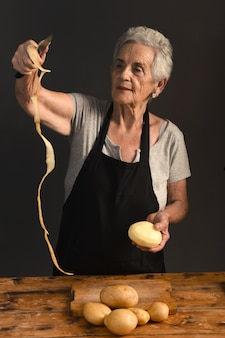 Senior woman peel potatoes