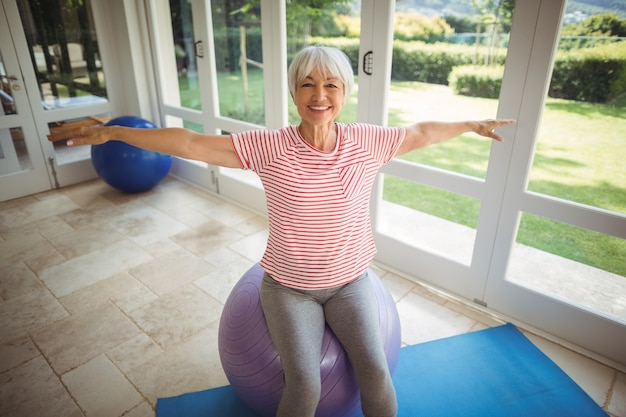 Senior woman performing stretching exercise on fitness ball