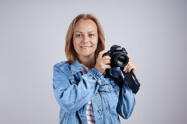 회색 배경에 전문 사진 카메라가 있는 수석 여성 사진사