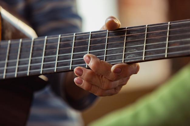 ギターを弾く年配の女性が時間を費やして手の自己開発白人女性をクローズアップ