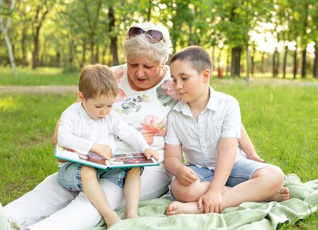 Старшая женщина играет с внуками на открытом воздухе. бабушка с внуками