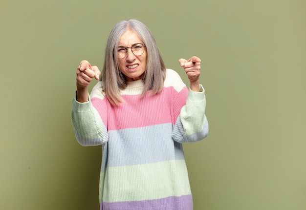 指と怒りの表情でカメラを前に向けて、義務を果たすように言っている年配の女性