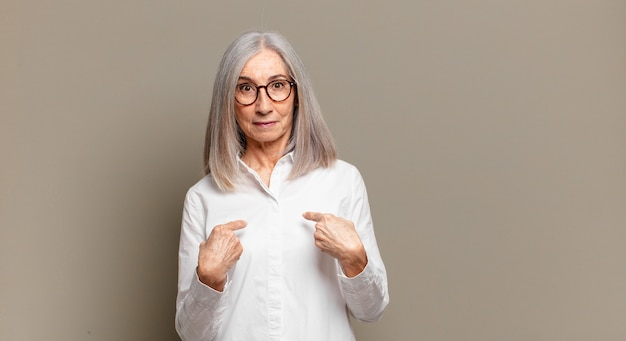 Senior woman pointing to self with a confused and quizzical look, shocked and surprised to be chosen