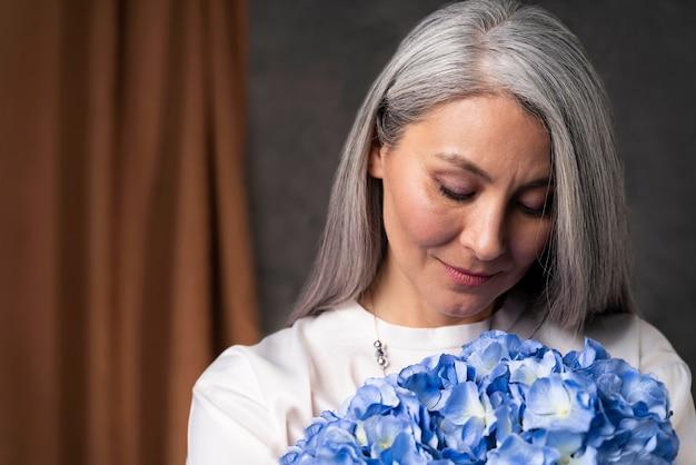 Ritratto di donna senior con bouquet di fiori