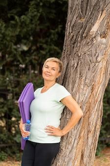 Старшая женщина позирует против дерева после тренировки