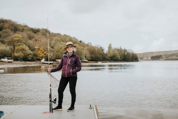 Senior woman posing with a fishing rod by the lake