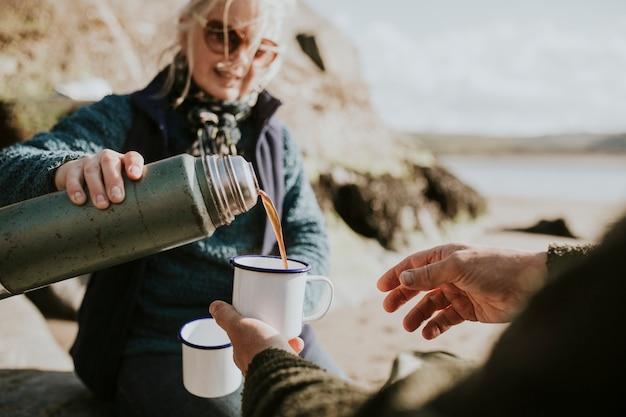 캠핑 머그잔에 커피를 붓는 고위 여자