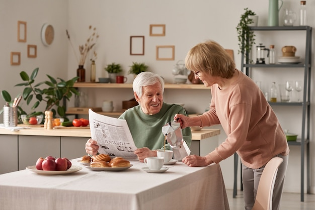 Senior woman pouring hot tea for her husband while he sitting at the table and reading newspaper during breakfast in the kitchen