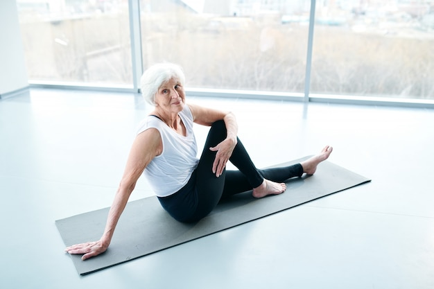 Senior woman practicing yoga next to a large window