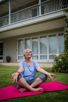 Senior woman practising yoga on exercise mat