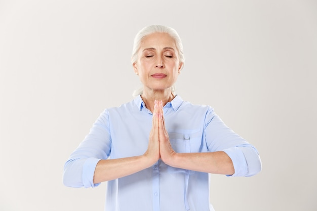 Senior woman practising yoga holding hands in namaste and keeping her eyes closed