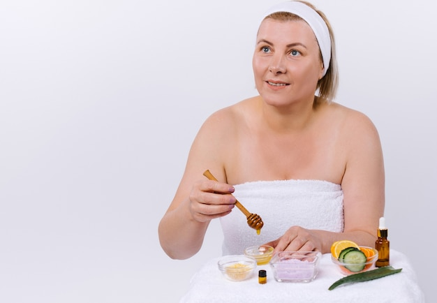 Senior woman prepares a face and body mask from natural products at home and looks away. home skin care. high quality photo