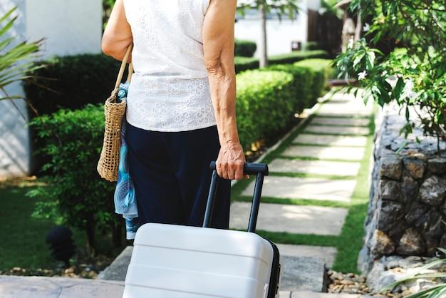 Старший женщина, потянув чемодан и ходить
