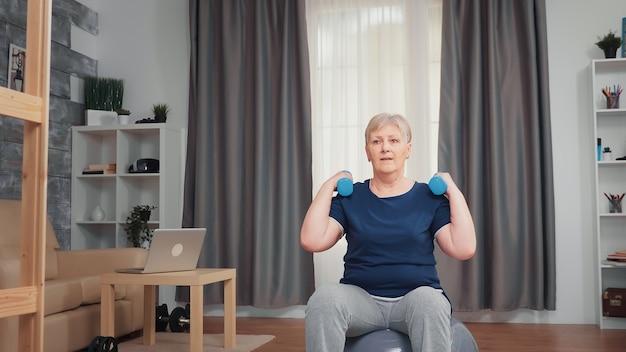 균형 공에 앉아 아령을 사용하여 어깨 근육을 펌핑 수석 여자. 홈 스포츠 건강한 생활 방식, 아파트, 활동 및 헬스카에서 노인 피트니스 운동 운동에서 노인 훈련