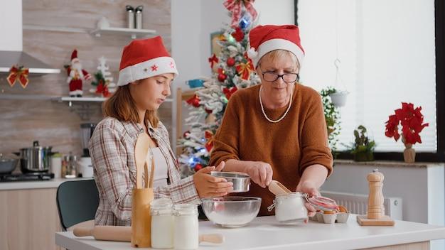孫娘がボウルに材料をふるいにかけている間、金属のsievに小麦粉を入れている年配の女性