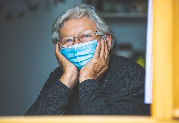 Пожилая женщина на карантине из-за коронавируса covid-2019 у себя дома, смотрит в окно